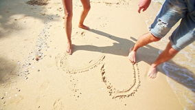 Ragazza Guy Feet Barefoot Draw Heart sulla spiaggia di sabbia al bordo di Wave archivi video