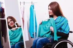 Ragazza handicappata sulla sedia a rotelle che sceglie i vestiti fotografia stock