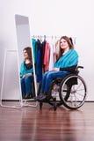 Ragazza handicappata sulla sedia a rotelle che sceglie i vestiti fotografia stock libera da diritti