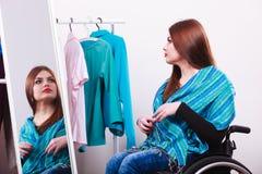 Ragazza handicappata sulla sedia a rotelle che sceglie i vestiti immagine stock libera da diritti