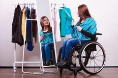 Ragazza handicappata sulla sedia a rotelle che sceglie i vestiti immagini stock libere da diritti