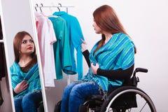 Ragazza handicappata sulla sedia a rotelle che sceglie i vestiti fotografie stock