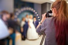 Ragazza il fotografo alle nozze Fotografie Stock Libere da Diritti