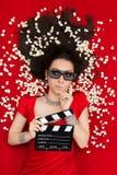 Ragazza imbarazzata con i vetri del cinema 3D, il popcorn e direttore Clapboard Fotografia Stock