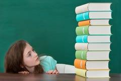 Ragazza impaurita che esamina i libri variopinti Fotografia Stock