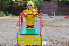Ragazza in impermeabile giallo sul campo da giuoco Fotografia Stock