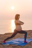 Ragazza incinta allegra che fa yoga all'aperto Immagini Stock