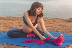 Ragazza incinta che fa allungamento con l'elastico Fotografie Stock