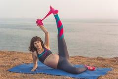 Ragazza incinta che fa allungamento con l'elastico Fotografia Stock