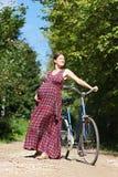 Ragazza incinta con la bicicletta su un sentiero forestale, vista frontale Immagini Stock
