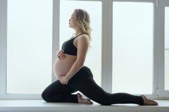 Ragazza incinta dei giovani che fa forma fisica sul davanzale della finestra fotografie stock libere da diritti