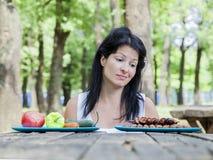 Ragazza incinta dei giovani che sceglie alimento per il suo pasto immagini stock