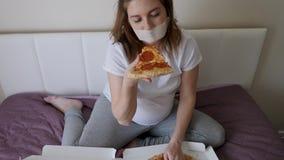 Ragazza incinta in maglietta bianca che si siede sul letto stock footage