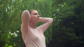 Ragazza incinta nel parco su un fondo del salice verde Colpi calmi della ragazza i suoi capelli, coprenti i suoi occhi da piacere archivi video