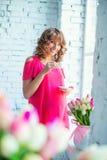 Ragazza incinta tenera in vestito rosa luminoso alla finestra Fotografie Stock