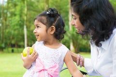 Ragazza indiana che giudica una mela verde all'aperto Immagine Stock