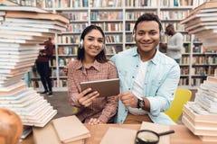 Ragazza indiana etnica e tipo della corsa mista circondati dai libri in biblioteca Gli studenti stanno utilizzando la compressa immagini stock