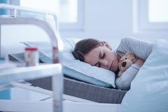Ragazza indisposta nel letto di ospedale fotografia stock libera da diritti