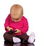 Ragazza infantile che gioca con un telefono delle cellule Fotografia Stock
