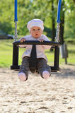Ragazza infantile nelle oscillazioni fotografia stock