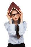 Ragazza infelice che tiene un libro sopra la sua testa Fotografie Stock
