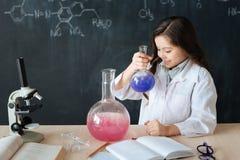 Ragazza intelligente che partecipa all'esperimento di chimica in laboratorio Immagini Stock