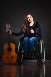 Ragazza invalida della donna sulla sedia a rotelle con la chitarra immagine stock