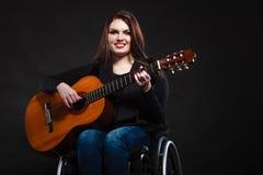 Ragazza invalida della donna sulla sedia a rotelle con la chitarra immagine stock libera da diritti