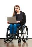 Ragazza invalida della donna sulla sedia a rotelle facendo uso del computer immagine stock