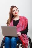 Ragazza invalida della donna sulla sedia a rotelle facendo uso del computer immagini stock libere da diritti