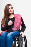 Ragazza invalida della donna sulla sedia a rotelle facendo uso della compressa immagini stock