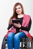 Ragazza invalida della donna sulla sedia a rotelle facendo uso della compressa immagine stock