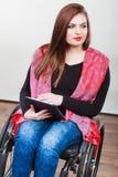 Ragazza invalida della donna sulla sedia a rotelle facendo uso della compressa fotografia stock libera da diritti