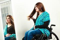 Ragazza invalida sulla sedia a rotelle che pettina capelli fotografie stock libere da diritti