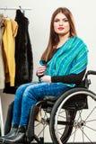 Ragazza invalida sulla sedia a rotelle che sceglie i vestiti in guardaroba fotografia stock
