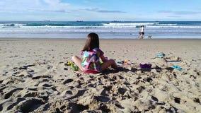 Ragazza irriconoscibile che gioca con i suoi giocattoli sulla spiaggia archivi video