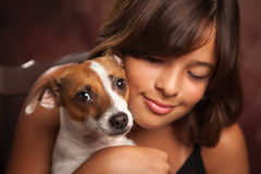 Ragazza ispana graziosa ed il suo ritratto dello studio del cucciolo fotografia stock