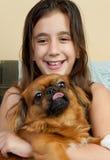 Ragazza ispanica che trasporta il suo piccolo cane pekingese Fotografia Stock