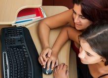 Ragazza ispanica e la sua madre che per mezzo di un calcolatore Fotografie Stock