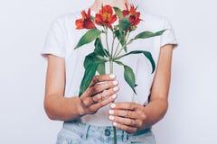 Ragazza in jeans e una maglietta che tiene un fiore rosso fotografia stock
