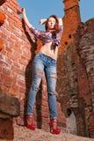 Ragazza in jeans lacerati nelle rovine Fotografia Stock
