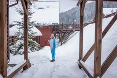 Ragazza in kigurumi blu e rosa di pijama dell'unicorno all'aperto davanti alle case di legno sul rapporto dello sci in montagne d fotografie stock