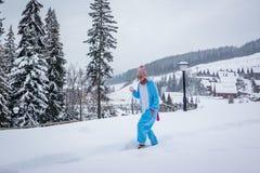 Ragazza in kigurumi blu e rosa di pijama dell'unicorno all'aperto davanti alle case di legno sul rapporto dello sci in montagne d immagini stock libere da diritti