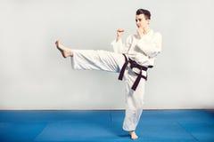 ragazza in kimono del vestito di karatè in studio a fondo grigio Il bambino femminile mostra che stans di karatè o di judo nel bi Immagini Stock Libere da Diritti