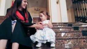 Ragazza laureata con il suo bambino nel corridoio dell'università stock footage