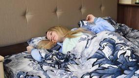 Ragazza a letto di mattina in pigiami blu