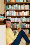 Ragazza in libro di lettura delle biblioteche immagine stock