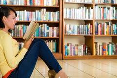 Ragazza in libro di lettura delle biblioteche immagini stock libere da diritti