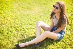 Ragazza lunga d'avanguardia dei capelli che si rilassa sull'erba immagini stock libere da diritti