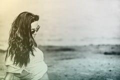 Ragazza lunga dei capelli che si rilassa sulla spiaggia immagini stock libere da diritti
